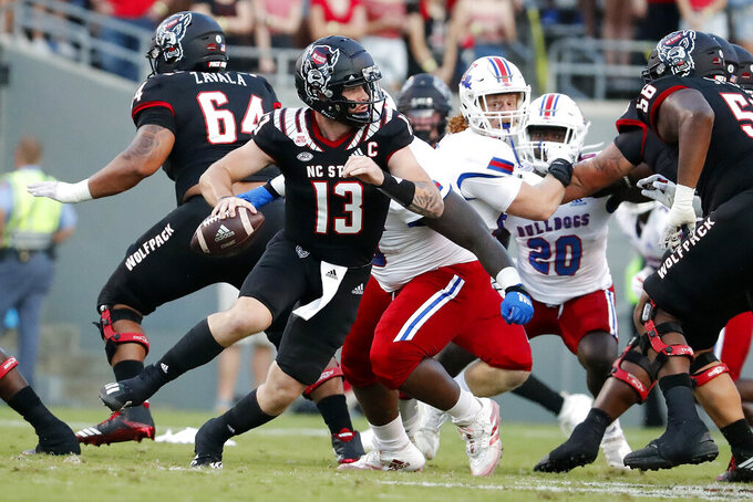 North Carolina State's Devin Leary (13) scrambles away from pressure by Louisiana Tech during the first half of an NCAA college football game in Raleigh, N.C., Saturday, Oct. 2, 2021. (AP Photo/Karl B DeBlaker)