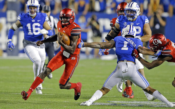 FILE - In this Sept. 9, 2017, file photo, Utah quarterback Tyler Huntley carries the ball as BYU defensive back Troy Warner (1) reaches for a tackle during the first half ofan NCAA college football game in Provo, Utah. Making more plays with his arm rather than his legs has become a primary goal for Huntley this season. (AP Photo/Rick Bowmer, File)