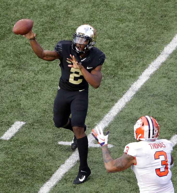 Wake Forest's Kendall Hinton (2) throws a pass under pressure from Clemson's Xavier Thomas (3) during the second half of an NCAA college football game in Charlotte, N.C., Saturday, Oct. 6, 2018. (AP Photo/Chuck Burton)