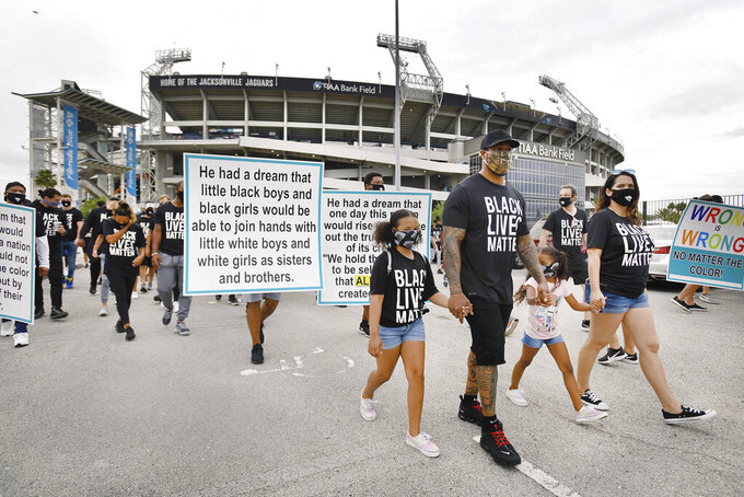 Jacksonville Jaguars assistant defensive line coach Dwayne Stukes walks with his family near the front of the line of players, staff and family members as they start a march from TIAA Bank Field to the Jacksonville Sheriff's office headquarters, Friday morning, June 5, 2020, in Jacksonville, Fla., to protest against inequality and police brutality. (Bob Self/The Florida Times-Union via AP)