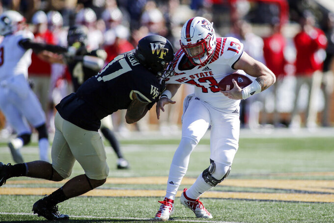 Wake Forest defensive back Traveon Redd, left, sacks North Carolina State quarterback Devin Leary in the first half of an NCAA college football game in Winston-Salem, N.C., Saturday, Nov. 2, 2019. (AP Photo/Nell Redmond)