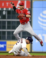 Los Angeles Angels shortstop Andrelton Simmons, top, leaps to avoid Houston Astros' Alex Bregman during a double play attempt during the third inning of a baseball game, Saturday, Sept. 21, 2019, in Houston. Yordan Alvarez was out at first. (AP Photo/Eric Christian Smith)