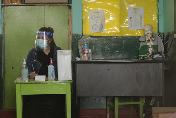 Wearing a mask and face shield, an electoral official waits for voters at a school being used as a polling station during general elections in Cuzco, Peru, Sunday, April 11, 2021. Peruvians went to the polls amid a surge in new COVID-19 infections. (AP Photo/Sharon Castellanos)