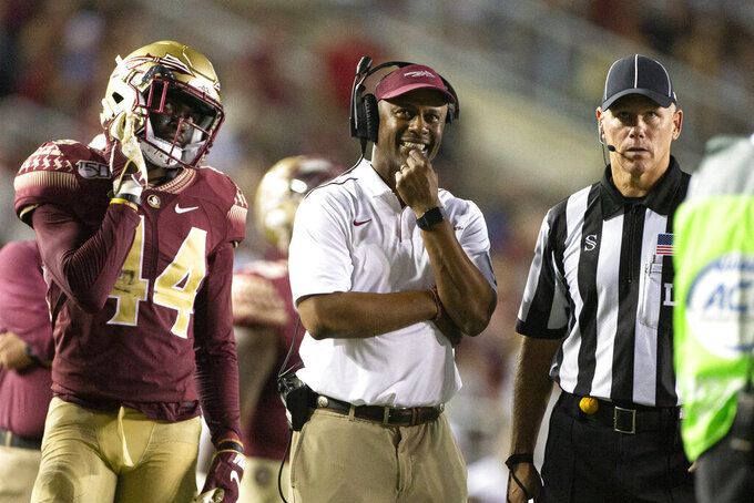 Florida State defensive back Brendan Gant (44), head coach Willie Taggart and an official watch the replays of a targeting penalty in the second half of an NCAA college football game against North Carolina State in Tallahassee, Fla., Saturday, Sept. 28, 2019. Florida State defeated North Carolina State 31-13. (AP Photo/Mark Wallheiser)