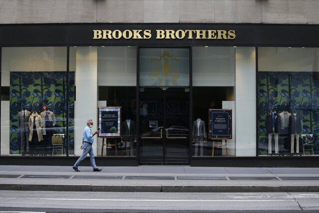 FILE - Pedestrians wearing protective masks walk past a Brooks Brothers location in a July 8, 2020 file photo, in New York. Brooks Brothers will be purchased for $325 million by a retail venture owned by licensing company Authentic Brands Group and mall owner Simon Property Group. It will continue running at least 125 Brooks Brothers retail locations as part of the deal. The 200-year-old New York-based clothier filed for Chapter 11 bankruptcy in July.  (AP Photo/Frank Franklin II, File)