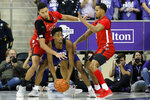 TCU guard RJ Nembhard, center, is double teamed by Texas Tech forward TJ Holyfield, left, and forward Tyreek Smith, right during the first half of an NCAA college basketball game in Fort Worth, Texas, Tuesday, Jan. 21, 2020. (AP Photo/Ray Carlin)