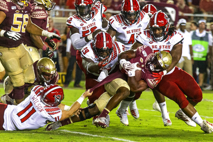 Florida State running back Khalan Laborn (4) charges ahead as he's brought down by North Carolina State linebacker Payton Wilson (11), defensive tackle Alim McNeill (29) and defensive tackle Larrell Murchison (92) in the first half of an NCAA college football game in Tallahassee, Fla., Saturday, Sept. 28, 2019. (AP Photo/Mark Wallheiser)