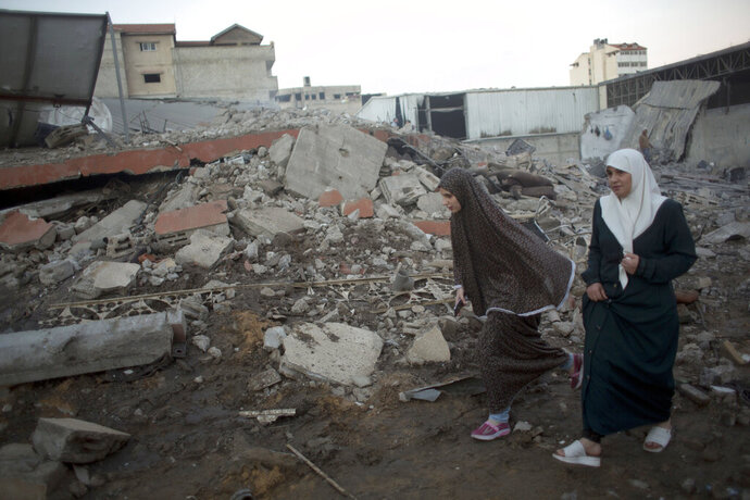 Two Palestinians women walk past the rubble of buildings destroyed by Israeli airstrikes early morning in Gaza City, Saturday, Oct. 27, 2018. Israeli aircraft have struck dozens of militant sites across the Gaza Strip as militants fired some 30 rockets into Israel. (AP Photo/Khalil Hamra)