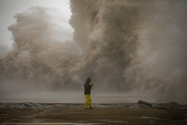 A woman photographs the Mediterranean sea as the waves hit the breakwater during a storm in Barcelona, Spain, Tuesday, Jan. 21, 2020. A winter storm lashed much of Spain for a third day Tuesday, leaving 200,000 people without electricity, schools closed and roads blocked by snow as it killed four people. Massive waves and gale-force winds smashed into seafront towns, damaging many shops and restaurants. (AP Photo/Emilio Morenatti)