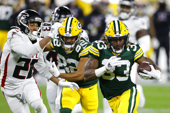 Green Bay Packers' Aaron Jones (33) is chased by Atlanta Falcons' Isaiah Oliver (26) during the first half of an NFL football game, Monday, Oct. 5, 2020, in Green Bay, Wis. (AP Photo/Tom Lynn)