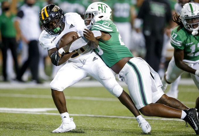 North Texas linebacker KD Davis (23) tackles Southern Mississippi running back Frank Gore Jr. (21) during the second half of an NCAA college football game on Saturday, Oct. 3, 2020 in Denton, Texas. (AP Photo/Brandon Wade)