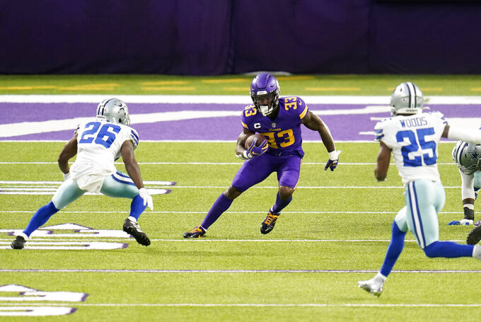 Minnesota Vikings running back Dalvin Cook (33) runs up field between Dallas Cowboys cornerback Jourdan Lewis (26) and safety Xavier Woods (25) during the first half of an NFL football game, Sunday, Nov. 22, 2020, in Minneapolis. (AP Photo/Jim Mone)