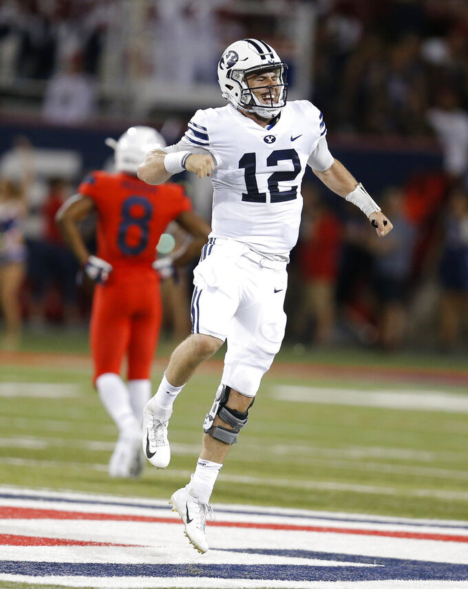Brigham Young quarterback Tanner Mangum (12) reacts after defeating Arizona 28-23 in the during an NCAA college football game, Saturday, Sept. 1, 2018, in Tucson, Ariz. (AP Photo/Rick Scuteri)
