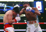Mikey Garcia, left, takes a blow to the head from Errol Spence Jr. during the 10th round of the IBF welterweight championship boxing bout Saturday, March 16, 2019, in Arlington, Texas. (AP Photo/Richard W. Rodriguez)