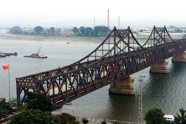 FILE - In this Sept. 4, 2017, file photo, trucks cross the friendship bridge connecting China and North Korea in the Chinese border town of Dandong, opposite side of the North Korean town of Sinuiju. China on Wednesday, Dec. 2, 2020, rejected U.S. accusations it is weakening its enforcement of sanctions against North Korea, but said more efforts are needed toward reaching a political settlement and greater attention should be paid to the impact of the sanctions on ordinary North Koreans. (AP Photo/Helene Franchineau, File)