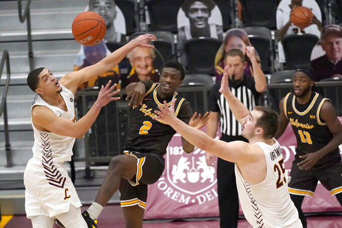 Valparaiso's Zion Morgan (2) passes under pressure from Loyola Chicago's Cameron Krutwig (25) and Lucas Williamson during the second half of an NCAA college basketball game Wednesday, Feb. 17, 2021, in Chicago. Loyola Chicago won 54-52. (AP Photo/Charles Rex Arbogast)