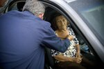 FILE - In this Sept. 28, 2017 file photo, Carmen Hernandez, who lives in a senior living facility that lacks water and electricity in the wake of Hurricane Maria, is evaluated by a doctor after she fell, as she sits still for the doctor inside a car parked outside the hospital for lack of space in Bayamon, Puerto Rico. Following the storm, disabled and elderly people were discharged from overwhelmed hospitals with bedsores that led to fatal infections. Medical oxygen ran out. People caught lung infections in sweltering private nursing homes and state facilities. Kidney patients got abbreviated treatments from dialysis centers that lacked generator fuel and fresh water, despite pleas for federal and local officials to treat them as a higher priority, according to patient advocates. (AP Photo/Ramon Espinosa, File)