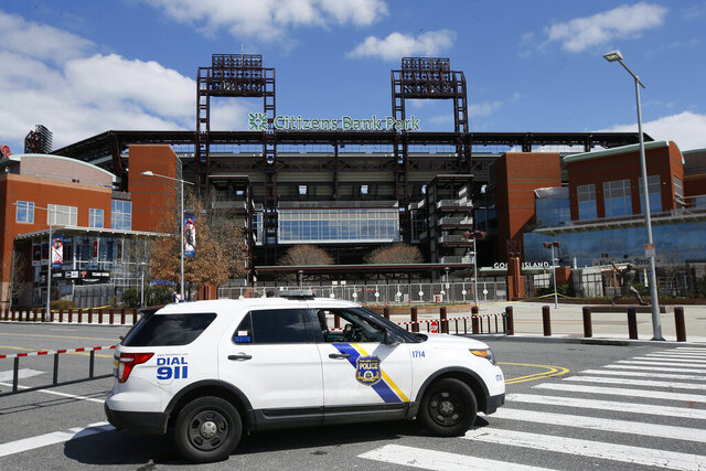 FILE - In this March 24, 2020, file photo, a Police vehicle blocks a street near Citizens Bank Park, home of the Philadelphia Phillies baseball team, in Philadelphia. On MLB's opening day, ballparks will be empty with the start of the season on hold because of the coronavirus pandemic. (AP Photo/Matt Slocum, File)