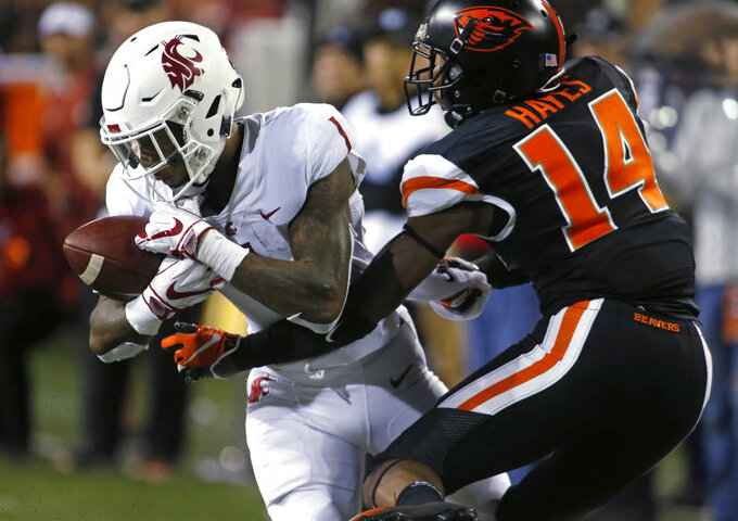 Washington State's Tay Martin (1) makes a catch in front of Oregon State's Kaleb Hayes during the fourth quarter of an NCAA college football in Corvallis, Ore., Saturday, Oct. 6, 2018. (AP Photo/Timothy J. Gonzalez)