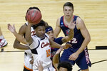 Oklahoma State forward Matthew-Alexander Moncrieffe (12) passes under pressure by Liberty's Elijah Cuffee, center, during the first half of a first round NCAA college basketball game Friday, March 19, 2021, at the Indiana Farmers Coliseum in Indianapolis.(AP Photo/Charles Rex Arbogast)
