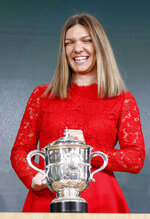 Defending champion Romania's Simona Halep smiles as she poses next to the cup during the draw of the French Open tennis tournament at the Roland Garros stadium in Paris, Thursday, May 23, 2019. The French Open tennis tournament starts Sunday May 26. (AP Photo/Michel Euler)