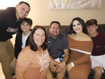 In this undated photo made available by Gary Troutt, Alan Arellano is surrounded by his wife Karyn, his children, Erick Hernandez, left, Evan Arellano, Alyssa Hernandez and A.J. Arellano. Alan, 49, died after suffering a heart attack while being treated for COVID-19. (Gary Troutt via AP)