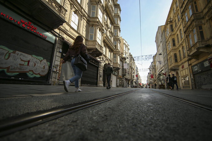 People walk on a virtually empty Istiklal Street, the main shopping street of Istanbul, with shops closed, Friday, April 30, 2021, on the first day of a tight lockdown to help protect from the spread of the coronavirus. Turkish security forces on Friday patrolled main streets and set up checkpoints at entry and exits points of cities, to enforce Turkey's strictest COVID-19 lockdown to date. Still, many people were on the move as the government, desperate not to shut down the economy completely, kept some sectors exempt from the restrictions. (AP Photo/Emrah Gurel)