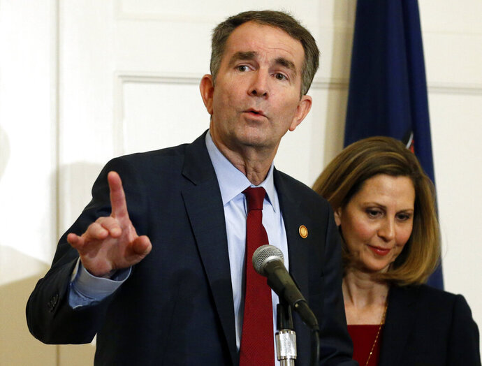FILE - In this Feb. 2, 2019 file photo Virginia Gov. Ralph Northam, left, gestures as his wife, Pam, listens during a press conference in the Governors Mansion at the Capitol in Richmond, Va. A commission Northam tasked with researching racist laws from the state's past recommended Thursday, Dec. 5, 2019, that dozens be repealed in order to purge the state's books of discriminatory language. (AP Photo/Steve Helber, File)