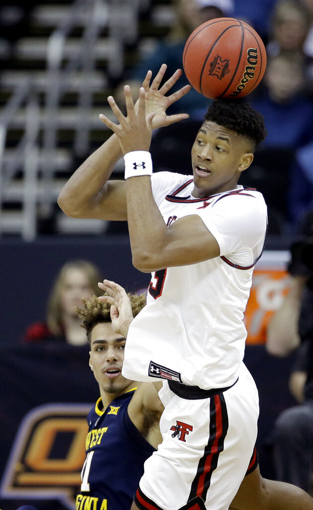 Texas Tech's Jarrett Culver, top, and West Virginia's Emmitt Matthews Jr. chase the ball during the first half of an NCAA college basketball game in the Big 12 men's tournament Thursday, March 14, 2019, in Kansas City, Mo. (AP Photo/Charlie Riedel)