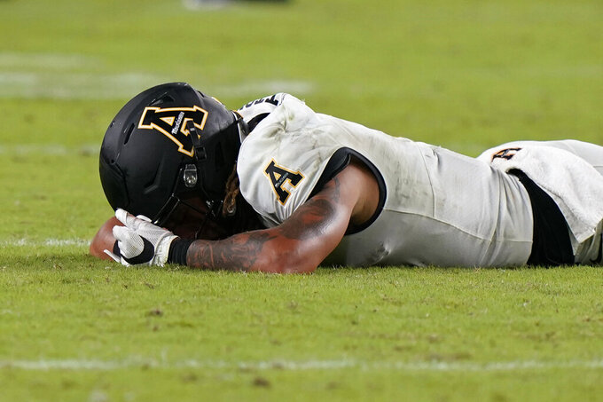 Appalachian State wide receiver Corey Xavier Sutton lies on the field after he was unable to catch a pass during the final minutes of the second half of an NCAA college football game against Miami, Saturday, Sept. 11, 2021, in Miami Gardens, Fla. (AP Photo/Wilfredo Lee)