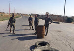 Four Syrian troops man a checkpoint at the entrance of the northwestern town of Khan Sheikhoun, Syria on Saturday, Aug. 24, 2019.  (AP Photo/Albert Aji)