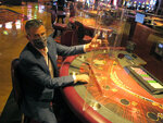 Ron Baumann, a regional president with Caesars Entertainment, sits at a card table at Harrah's casino on July 1, 2020,  in Atlantic City, N.J., where plexiglass barriers have been installed to separate gamblers to prevent the spread of the coronavirus. On Monday, Jan. 25, 2021, the company replaced Baumann, who had overseen the Caesars and Harrah's casinos, with two new executives. (AP Photo/Wayne Parry)