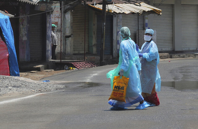 Indian health workers walk inside a containment zone during lockdown to prevent the spread of new coronavirus in Hyderabad, India, Sunday, April 26, 2020. A month long restrictions in this country of 1.3 billion people have been eased somewhat by allowing neighborhood shops to reopen and manufacturing and farming activities to resume in rural areas to help millions of poor daily wage earners. (AP Photo/Mahesh Kumar A.)