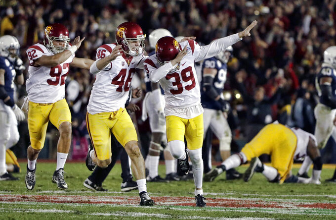 FILE - In this Jan. 2, 2017, file photo, Southern California place kicker Matt Boermeester (39) celebrates after kicking the game winning field goal against Penn State during the second half of the Rose Bowl NCAA college football game, in Pasadena, Calif. The fun starts for those who did get into the postseason _ and those who get to watch it _ Saturday with five FBS bowl games and stretches through New Year's Day. (AP Photo/Gregory Bull, File)