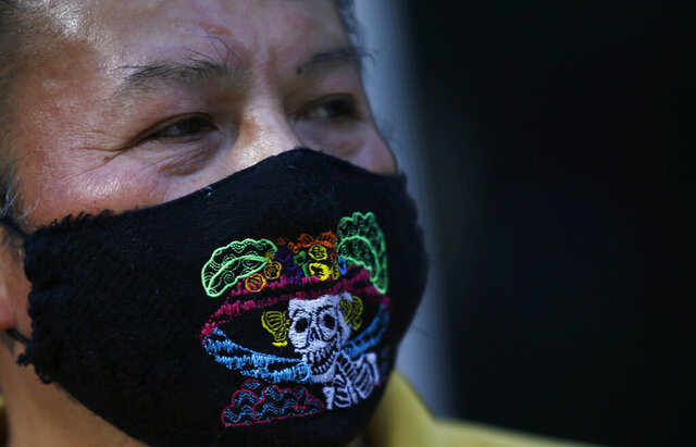Pedro Nuñez wears a mask embroidered with the image of a