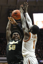 Purdue forward Trevion Williams (50) goes up to pass around Texas guard Andrew Jones (1) in the second half of an NCAA college basketball game in West Lafayette, Ind., Saturday, Nov. 9, 2019. Texas won 70-66. (AP Photo/AJ Mast)