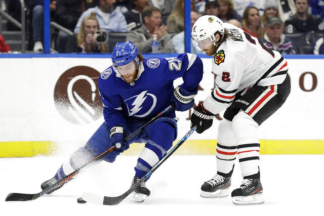 Tampa Bay Lightning center Brayden Point (21) tries to get around Chicago Blackhawks defenseman Duncan Keith (2) during the second period of an NHL hockey game Thursday, Feb. 27, 2020, in Tampa, Fla. (AP Photo/Chris O'Meara)