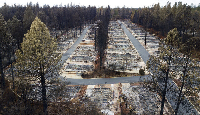 File - In this Dec. 3, 2018, file photo, are homes leveled by the Camp Fire line the Ridgewood Mobile Home Park retirement community in Paradise, Calif. A $13.5 billion settlement covering most of the losses from a series of catastrophic wildfires that drove Pacific Gas and Electric into bankruptcy is turning into a financial tug of war pitting the interests of U.S. taxpayers against the disaster victims still trying to rebuild their lives. (AP Photo/Noah Berger)