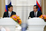 Cambodian Prime Minister Hun Sen, right, talks with his Laos counterpart Thonloun Sisoulith during a press conference, in Phnom Penh, Cambodia, Thursday, Sept. 12, 2019. Thonloun Sisoulith is on his two-day official visit to Cambodia. (AP Photo/Heng Sinith)