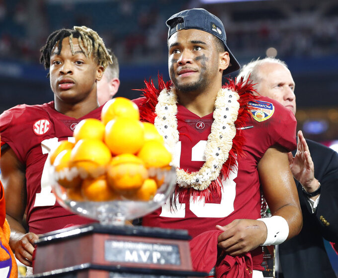 Alabama quarterback Tua Tagovailoa (13) stands next to the MVP trophy for the offensive player of the game at the end of the Orange Bowl NCAA college football game against Oklahoma , Sunday, Dec. 30, 2018, in Miami Gardens, Fla. Alabama defeated Oklahoma 45-34. (AP Photo/Wilfredo Lee)