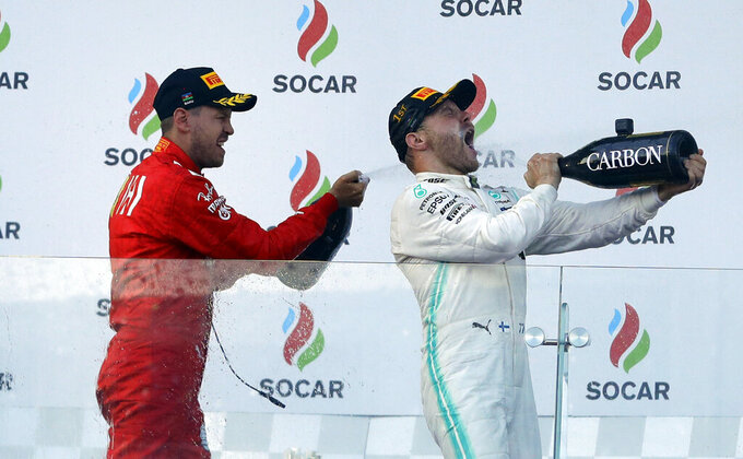 Mercedes driver Valtteri Bottas of Finland, right, celebrates with third placed Ferrari driver Sebastian Vettel of Germany after winning the Formula One Grand Prix at the Baku Formula One city circuit in Baku, Azerbaijan, Sunday, April 28, 2019. (AP Photo/Sergei Grits)