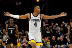 Iowa guard Bakari Evelyn reacts after scoring a 3-point basket against Cincinnati during the second half of an NCAA college basketball game Saturday, Dec. 21, 2019, in Chicago. (AP Photo/Matt Marton)