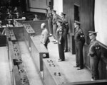 Hideki Tojo, former prime minister of Japan and war leader, stands in the dock before the International Military Tribunal in Tokyo on Nov. 12, 1948, to hear himself sentenced to death by hanging for his war crimes. Behind Tojo is Lieut. Col. Aubrey S. Kenworthy, who is responsible for the prisoners. Military police line the rear rail of the dock. The declassified U.S. military documents show the ashes of seven executed war criminals, including wartime Prime Minister Tojo, were scattered at sea off Yokohama from  a U.S. army plane. (AP Photo/Charles Gorry)