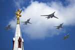 Russia's Air Force strategic bombers, Tu-160, center, and Tu-22M3, all others, fly over Red Square during the Victory Day military parade marking the 75th anniversary of the Nazi defeat in WWII, in Moscow, Russia, Wednesday, June 24, 2020. The Victory Day parade normally is held on May 9, the nation's most important secular holiday, but this year it was postponed due to the coronavirus pandemic. (AP Photo/Pavel Golovkin, Pool)