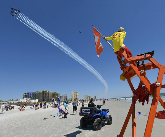 The U.S Navy's Blue Angels fly over as Jacksonville Beach Police Officer Thomas Harper and lifeguard Josh Mullis look on Friday, May 8, 2020 in Jacksonville Beach, Fla. The flyover was a salute to first responders in the wake of the coronavirus pandemic. (Will Dickey/The Florida Times-Union via AP)