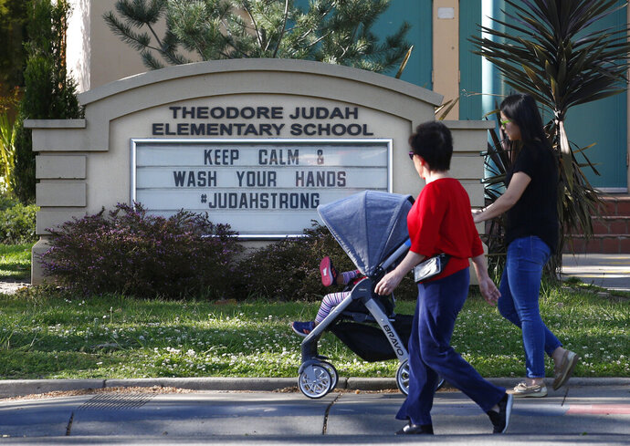 FILE - In this April 1, 2020, file photo, a reminder for people to wash their hands is displayed on a sign outside Theodore Judah Elementary School in Sacramento, Calif. California will allow schools, day camps, bars, gyms, campgrounds and professional sports to begin reopening with modifications starting Friday, June 12, 2020. (AP Photo/Rich Pedroncelli, File)
