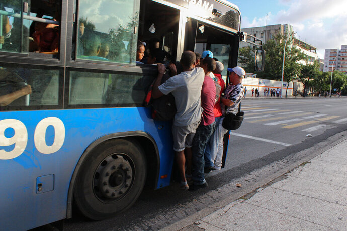 Locals hang precariously from a public service bus in Havana, Cuba, Wednesday, Sept. 11, 2019. The island nations is facing a diesel fuel shortage, but the government said there will be no electricity blackouts. The government blames the recent economic sanctions placed by the U.S. Trump administration for this latest energy crisis. (AP Photo/Ismael Francisco)