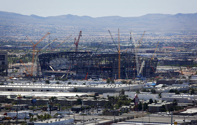 FILE - In this June 4, 2019, file photo, construction cranes surround the football stadium under construction in Las Vegas. Officials say installation of a translucent roof is behind schedule on the $2 billion football stadium being built in Las Vegas for the relocated NFL Raiders. The Las Vegas Review-Journal reports that Raiders team and construction officials are expected to provide an update on Thursday, Jan. 16, 2020. to the Las Vegas Stadium Authority about the cover for 65,000-seat indoor Allegiant Stadium. Team officials say the stadium is still on track to open July 31, in time to host a first scheduled event Aug. 16. (AP Photo/John Locher, File)