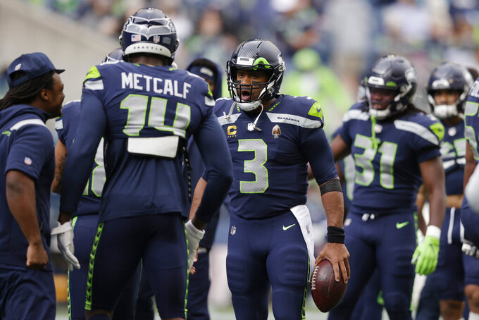 Seattle Seahawks quarterback Russell Wilson (3) greets wide receiver DK Metcalf (14) during warmups before an NFL football game against the Tennessee Titans, Sunday, Sept. 19, 2021, in Seattle. (AP Photo/John Froschauer)