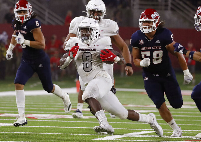 UNLV running back Charles Williams, center, runs for a big gain against Fresno State during the second half of an NCAA college football game in Fresno, Calif., Friday, Sept. 24, 2021. (AP Photo/Gary Kazanjian)